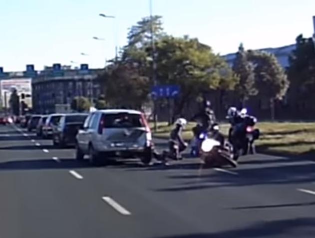 policjant na motocyklu doprowadza do wypadku